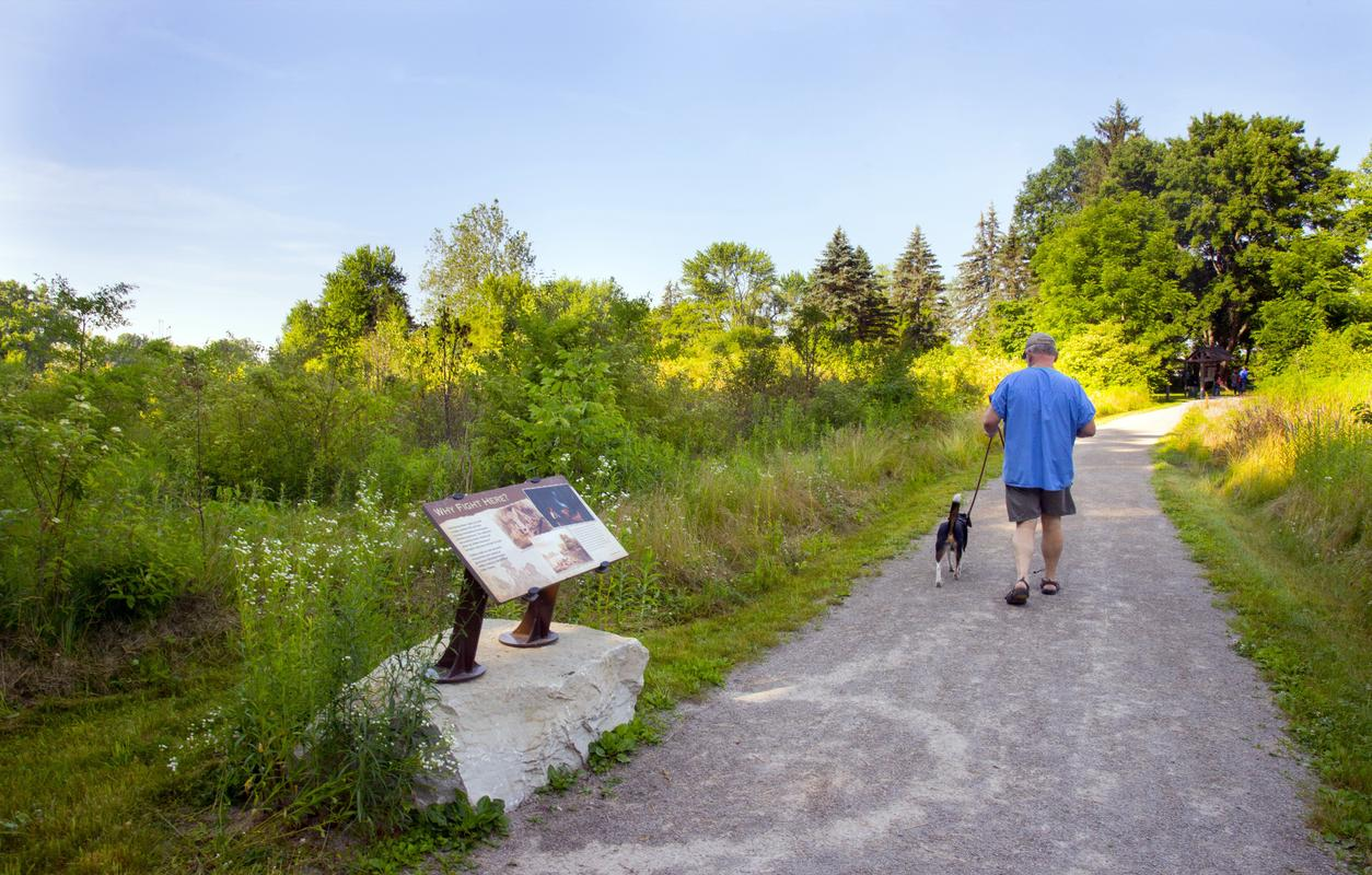 Man walks his dog along a trail at the historic Fallen Timbers Battlefield and Visitors Center.