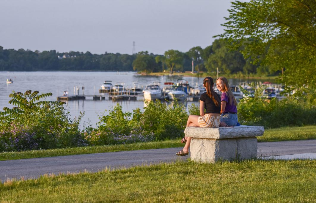 Friends catching up on a bench at Perrysburg Riverside Park with water and docked boats in the distance.
