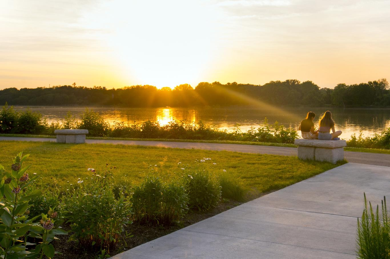 Young women watching the sunset at Perrysburg's multi-level riverfront park pathways that echo the river.